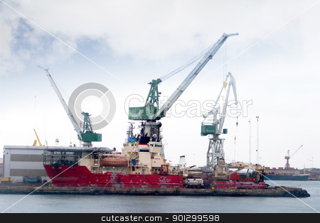 Cargo Ship at Dock stock photo, A large old transport ship being loaded. by Tyler Olson