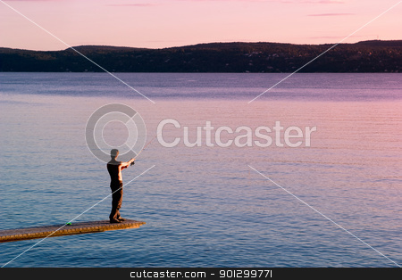 Fishing stock photo, A young man fishing in the ocean at sunset by Tyler Olson