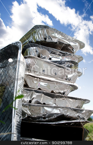 Tinfoil Disposable BBQ Garbage stock photo, A stack of tinfoil disposable barbcues against a blue summer sky by Tyler Olson