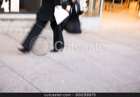Business Woman on Sidewalk stock photo, A business woman quickly walking.  Motion blur is used to create the photograph. by Tyler Olson