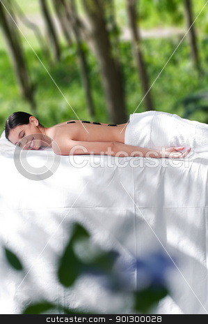 Attractive woman getting spa treatment stock photo, Beautiful young girl at the day spa with black stones on her bare back by Tyler Olson