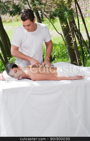 Man giving massage to woman by a wooden massager stock photo, Young man giving massage to woman by a wooden massager by Tyler Olson