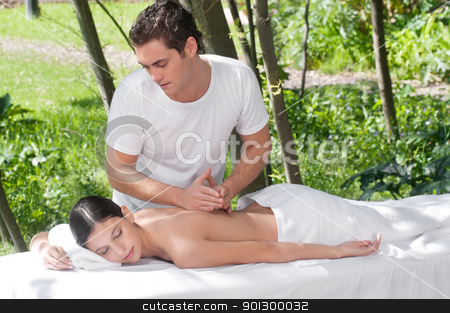 Outdoor Massage Therapy stock photo, Woman receiving massage outdoors from professional masseuse by Tyler Olson