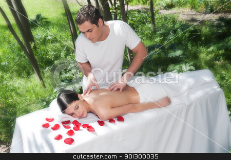 Young woman getting a back massage stock photo, Beautiful woman getting massage and spa treatment in natural setting by Tyler Olson