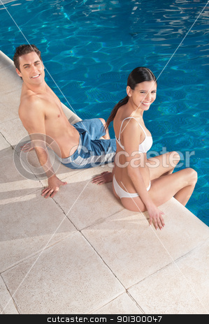 Smiling couple sitting near pool stock photo, An attractive young smiling couple relaxing by the pool by Tyler Olson