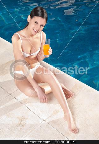 Woman holding orange juice stock photo, Young female with orange juice sitting near swimming pool by Tyler Olson