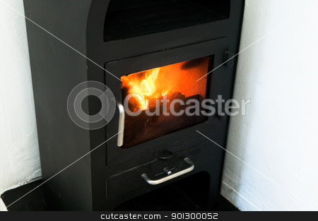 Efficient Fireplace stock photo, An efficient small metal fire place burning a log. by Tyler Olson