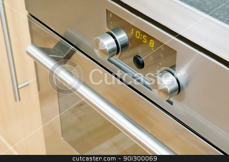 Modern Oven Detail stock photo, A modern stainless steel oven detail showing the knobs and door by Tyler Olson