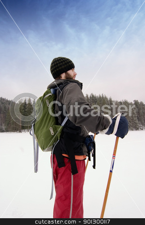 Confident Beginner Skiier stock photo, A confident cross country skiier out on a refreshing trip over a frozen lake with a backpack by Tyler Olson