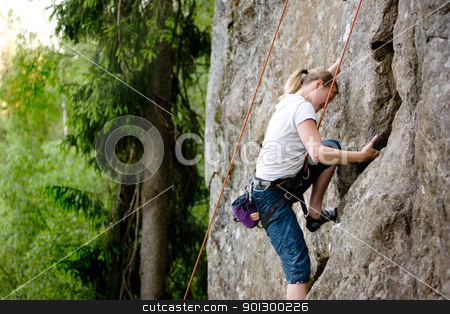 Female Climber stock photo, A female climber, climbing using a top rope on a steep rock face (crag) by Tyler Olson