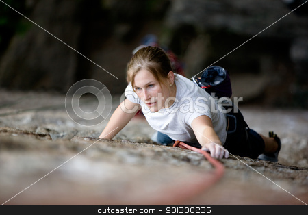 Female Climber stock photo, A female climber on a steep rock face looking for the next hold.  Shallow depth of field is used to isolate the climber. by Tyler Olson