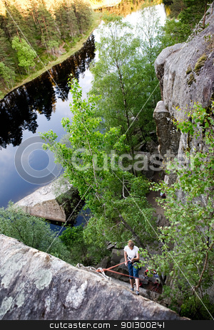 Female Climber stock photo, A female climber, repelling down a steep rock face (crag) by Tyler Olson