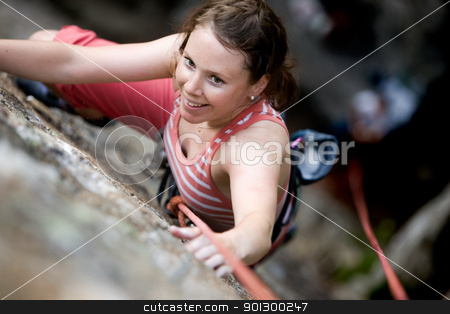 Female Climber stock photo, A female climber on a steep rock face viewed from above with the belayer in the background.  The climber is smiling at the camera. Shallow depth of field is used to isolated the climber. by Tyler Olson