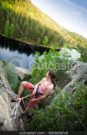 Success with a View stock photo, A female climber on a steep rock face viewed from above with the belayer in the background.  The climber has proudly reached the top. Shallow depth of field is used to isolated the climber. by Tyler Olson