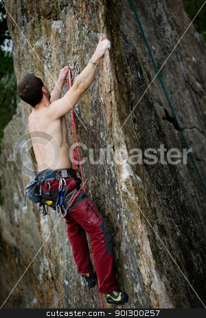Male Rock Climber stock photo, A male climber, viewed from above, climbs a very high and steep crag.  The image is taken as the climber clips into the bolt. by Tyler Olson