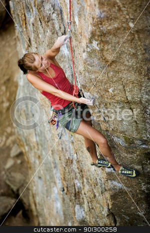 Female Climber stock photo, A female climber, viewed from above, climbs a very high and steep crag.  by Tyler Olson