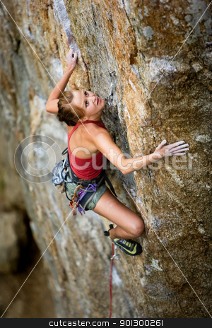Female Climber stock photo, An eager female climber on a steep rock face looks for the next hold - viewed from above.  Shallow depth of field is used to isolated the climber. by Tyler Olson