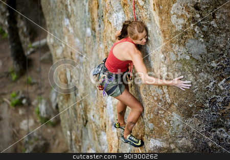 Female Climber stock photo, An eager female climber on a steep rock face looks for the next hold - viewed from above.  Shallow depth of field is used to isolated the climber with the focus on the head. by Tyler Olson
