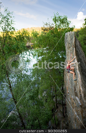 Female Climber stock photo, An eager female climber on a steep rock face looks for the next hold. Breathtaking scenery including a lake and forest are in the background. Shallow depth of field is used to isolated the climber with the focus on the head. by Tyler Olson