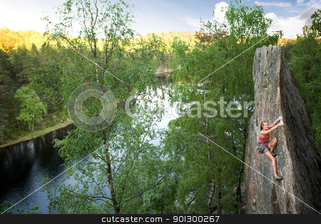 Female Climber stock photo, An happy female climber on a steep rock face looks at the camera and smiles - viewed from above.  Shallow depth of field is used to isolated the climber with the focus on the head. by Tyler Olson