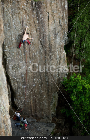 Male Rock Climber stock photo, A male climber against a large rock face climbing lead. by Tyler Olson