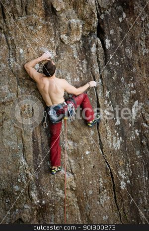 Male Rock Climber stock photo, A male climber against a large rock face climbing lead against a magnificant landscape. by Tyler Olson