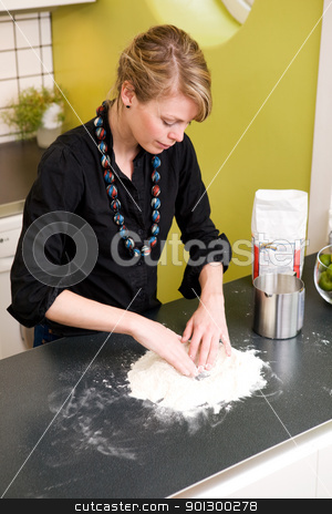 Woman Making Bread at Home stock photo, A young woman makes bread on the counter at home in the kitchen. by Tyler Olson
