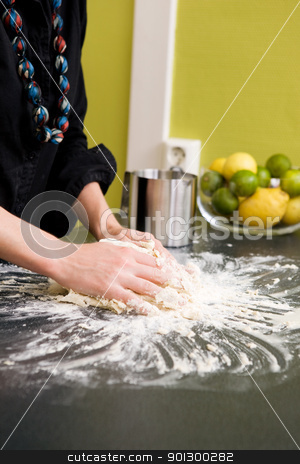 Kneading Dough with Hands stock photo, A young woman makes bread on the counter at home in the kitchen. by Tyler Olson