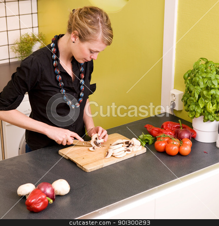 Woman Cutting Vegetables stock photo, A woman cutting vegetables at home on the counter by Tyler Olson