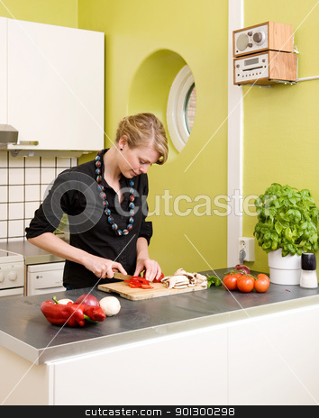 Woman Cutting Vegetables stock photo, A woman feeling happy and cutting vegetables at home on the counter. by Tyler Olson