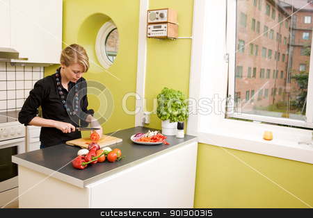 Preparing Supper stock photo, A female in her apartment kitchen preparing supper and cutting tomatoes; by Tyler Olson