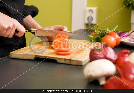 Slicing Tomatoes Detail stock photo, A detail image of a woman slicing tomatoes on a cutting board at home. - shallow depth of field with the focus on the tomato and knife by Tyler Olson