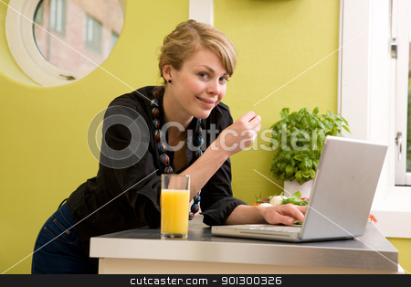 Lunch while Surfing stock photo, A female smiles at the camera while eating halthy lunch and using the computer by Tyler Olson