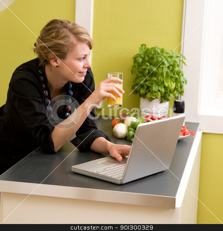 Lunch with Laptop stock photo, A female eating lunch while using the laptop at home in the kicthen. by Tyler Olson