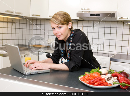 Modern Lunch stock photo, A young female eats a healthy lunch of vegetables at the kitchen counter while using the computer. by Tyler Olson