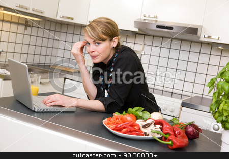 Lunch in Kitchen with Laptop stock photo, A young female woman using the computer in the kitchen over a small healthy lunch. by Tyler Olson