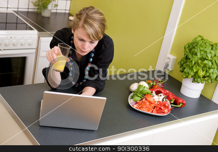 Concerned over Lunch stock photo, A young woman looks concered while using the computer and eating a healthy lunch of vegetables and juice. by Tyler Olson