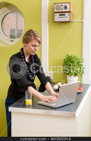 Computer in Kitchen stock photo, A female uses the computer on the kitchen counter while having a light snack of vegetables by Tyler Olson