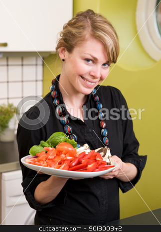 Freshly Cut Vegetables stock photo, A female in the kitchen looking down on a tasty plate of vegetables by Tyler Olson