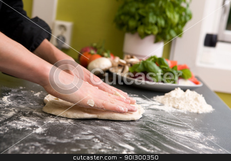 Hands making pizza - detail stock photo, A pair of female hands prepare some bread dough on the counter for pizza. by Tyler Olson