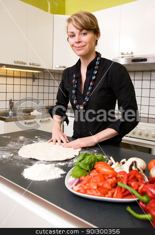 Young Woman Making Pizza Dough stock photo, A young woman is making pizza dough on the kitchen counter at home in her apartment. Shallow depth of field with focus on the models face and hands. by Tyler Olson