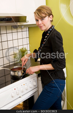 Female in Kitchen stock photo, A female in the kitchen stiring a sauce over the stove. by Tyler Olson