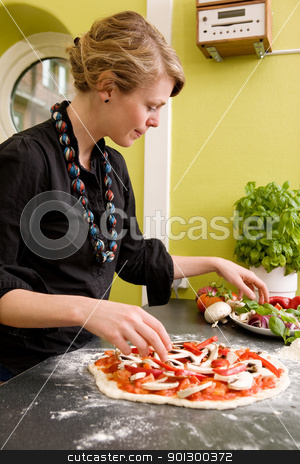 Homemade Italian Style Pizza stock photo, A young female making an italian style pizza at home in her apartment kitchen. by Tyler Olson