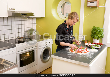 Young Female Making Pizza stock photo, A young female in an apartment kitchen making an itialian style pizza. by Tyler Olson