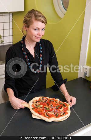 Fresh Pizza stock photo, A young woman presents a homemade italian style pizza fresh from the oven in her apartment kitchen. by Tyler Olson