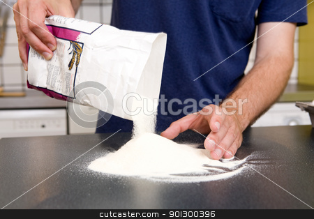 Making Pasta - Pouring Flour stock photo, A young man making pasta at home in an apartment kitchen. by Tyler Olson