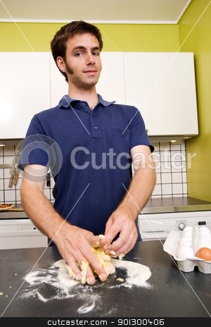 Happy Pasta Making stock photo, A happy male in the kitchen making pasta by hand and getting messy by Tyler Olson