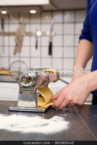 Rolling Pasta Detail stock photo, A woman rolling pasta at home in the kitchen by Tyler Olson