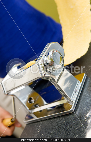 Pasta Machine stock photo, A young female stretching out pasta over the counter from a manual pasta machine at home in the kitchen. by Tyler Olson