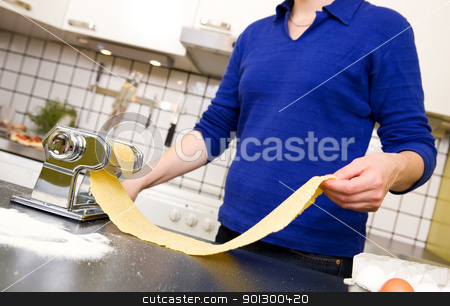 Female Making Pasta stock photo, A young female stretching out pasta over the counter from a manual pasta machine at home in the kitchen. by Tyler Olson